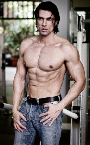Handsome muscular man in jeans shirtless looking away